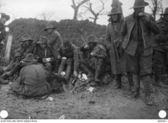 A fatigue party of the 22nd Battalion, road mending between Montauban and Mametz, having their midday meal by the roadside, December 1916 (AWM)